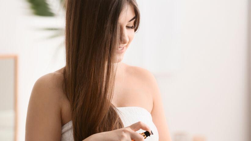 Kobieta z długimi włosami nakłada odżywkę na włosy