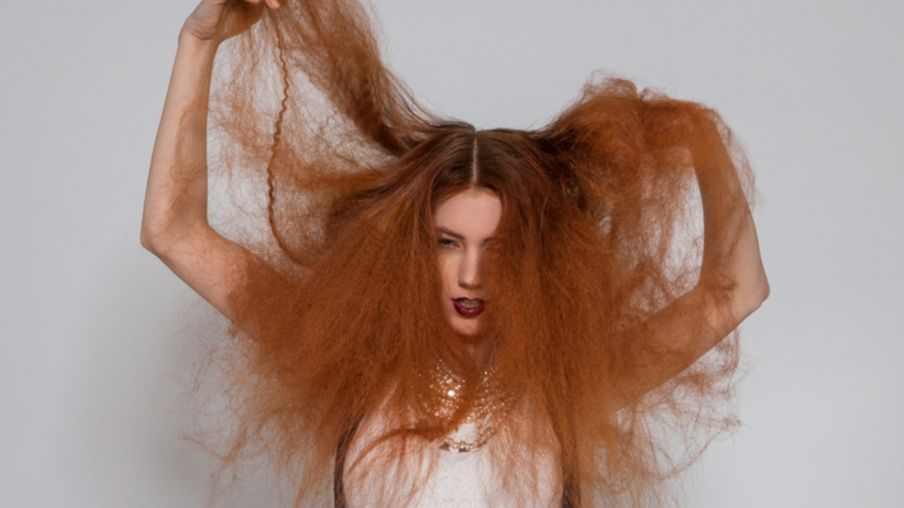 Puszące się włosy w kolorze rudym i kobieta, która na nie narzeka