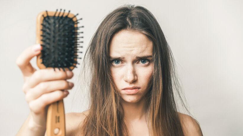 Sfrustrowana młoda dziewczyna pokazuje na szczotce, że bardzo wypadają jej włosy