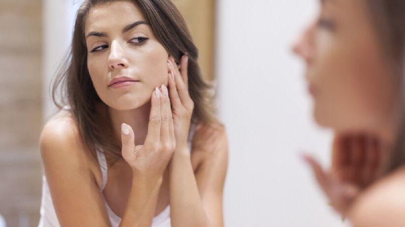 Kobieta ogląda trądzik na twarzy