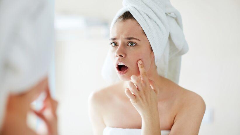 Kobieta ogląda skórę twarzy
