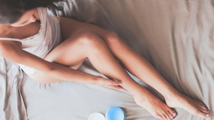 Piękna kobieta smaruje balsamem nogi, siedząc na łóżku