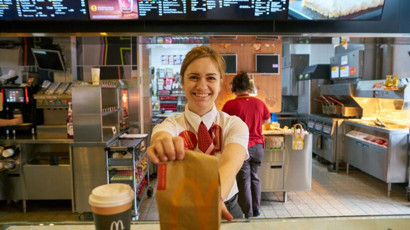 Kobieta pracująca w McDonald's podaje jedzenie w papierowej torbie
