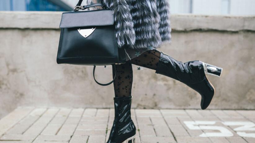 Kobieta z rajstopami w gwiazdki, w sztucznym futrze i botkach na jesień spaceruje ulicą