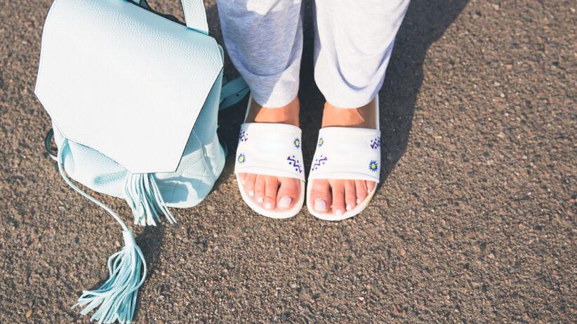 Kobieta w białych klapkach z kolorowymi wzorami, z pomalowanymi na biało paznokciami u stóp i niebieskim plecaczkiem