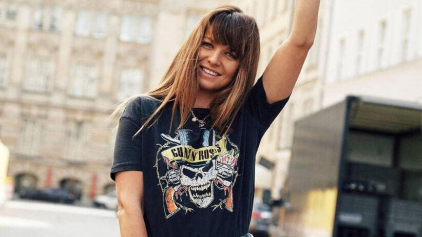 Anna Lewandowska w koszulce Guns'N'Roses i przewiązanej w pasie koszuli w kratę pozuje z victorią do góry na mieście