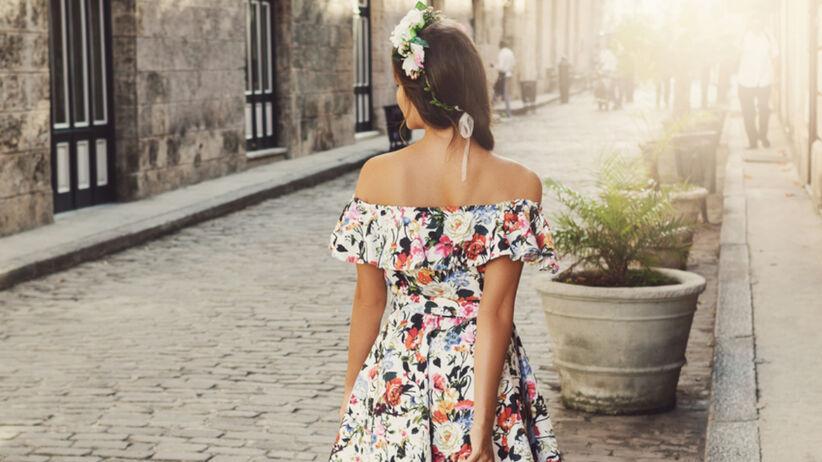 Młoda dziewczyna z długimi włosami w sukience hiszpance w kwiaty i z wiankiem na głowie