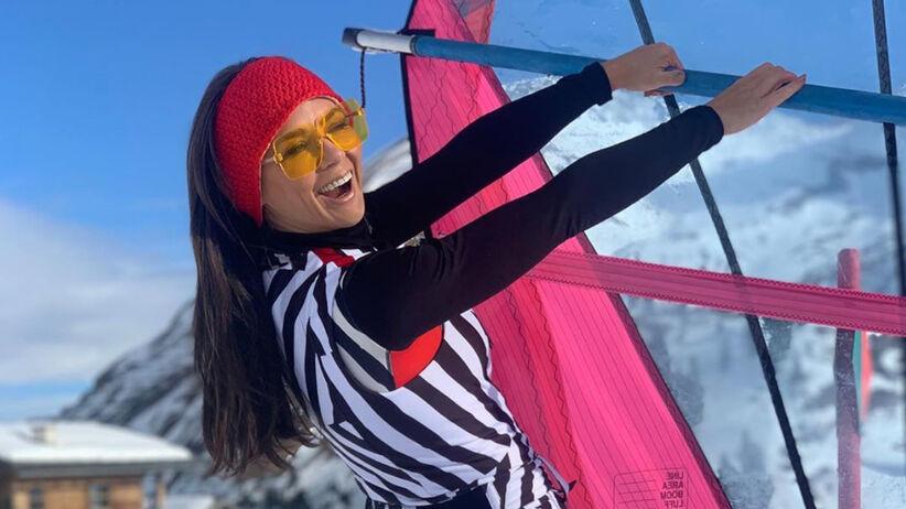 Kinga Rusin w kombinezonie w paski, czerwonej kurtce i goglach narciarskich w Alpach
