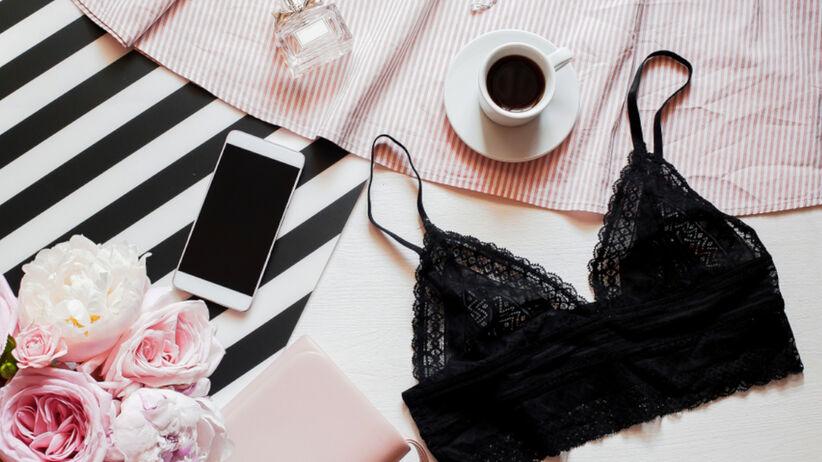 Koronkowa bielizna leży na stole w towarzystwie kwiatów i perfum
