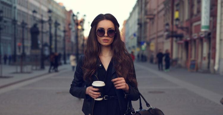 Młoda brunetka w czarnej sukience i rajstopach z czarną torbą i papierowym kubkiem kawy idzie po mieście