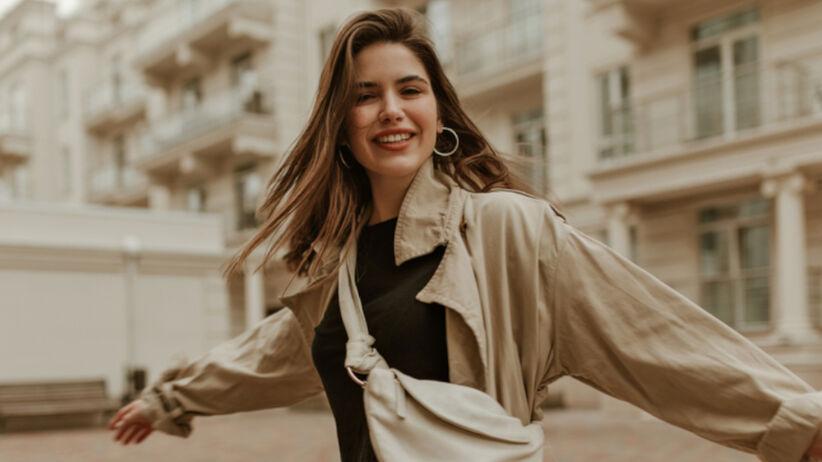 Uśmiechnięta dziewczyna w spódnicy w kratę i beżowym trenczu jesienią