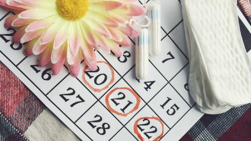 Jak przyśpieszyć okres - na blacie leży kalendarz oraz wkładki higieniczne.