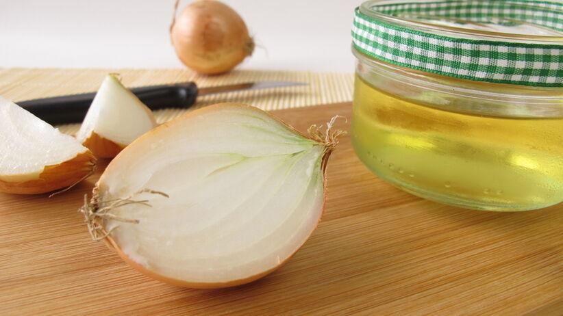 Na drewnianym blacie leży cebula i sok z teko warzywa.