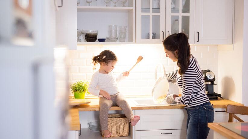 Mama z córką gotują razem w małej, białej kuchni