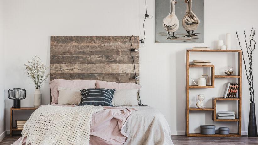 Sypialnia z dużym łóżkiem z różową pościelą oraz obrazem wiszącym na ścianie
