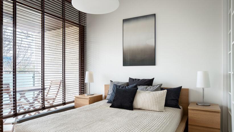 Sypialnia z dużym łóżkiem i czarnymi roletami