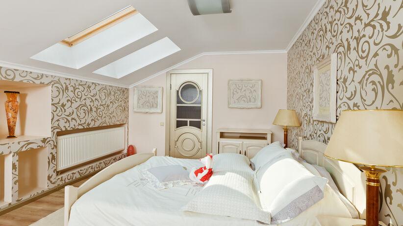 Sypialnia ze skosem z dużym łóżkiem z białą pościelą