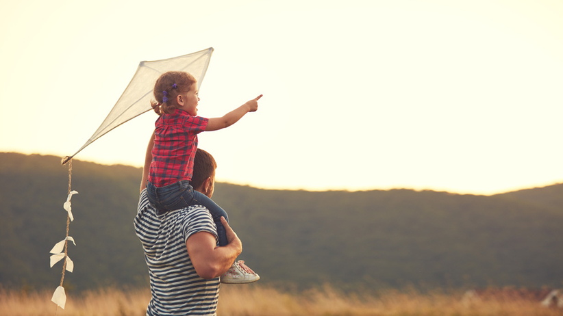 Dziecko z ojcem bawi się latawcem