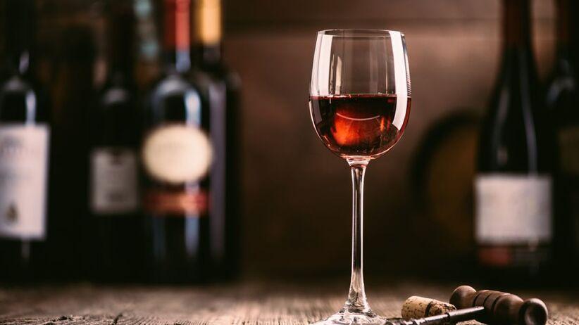 Kieliszek z czerwonym winem na stole.