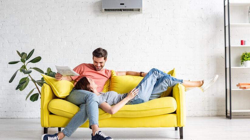 Szczęśliwa para leży na żółtej kapanie w swoim mieskzaniu
