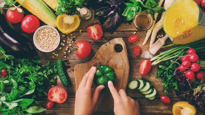 Kucharz kroi warzywa na desce do krojenia w swojej kuchni