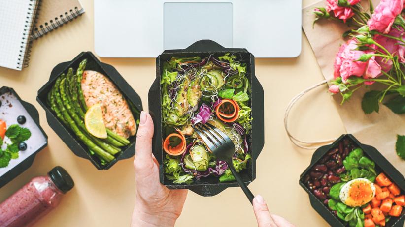 Catering dietetyczny w pudełkach - różne posiłki na biurku obok laptopa i kwiatów