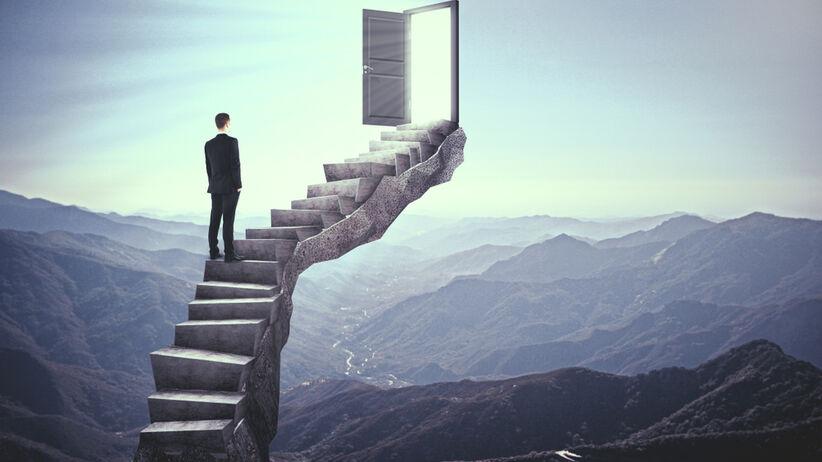 Meżczyzna idący po abstrakcyjnych schodach w stronę drzwi