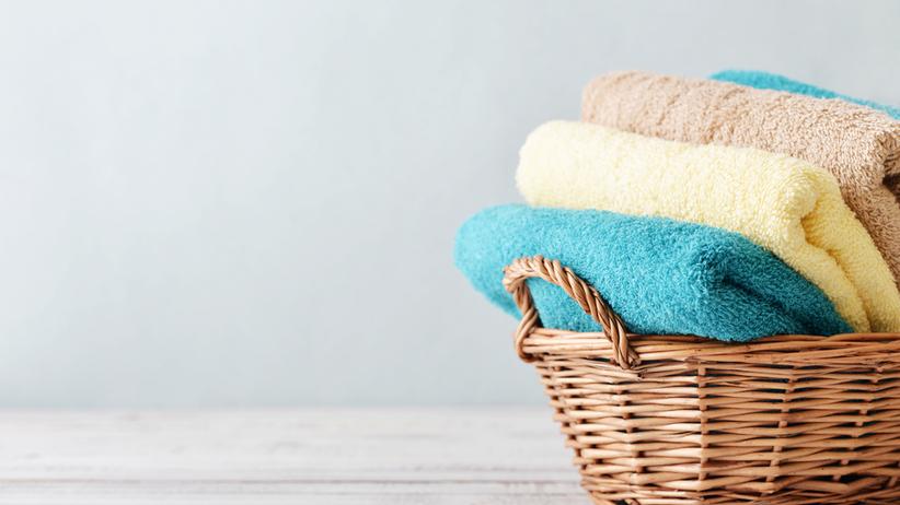 Kolorowe ręczniki w wiklinowym koszu