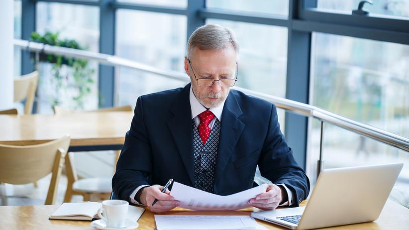 Mężczyzna w okularach siedzący przy biurku