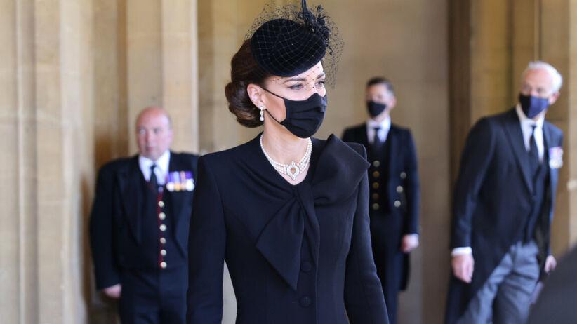 Księżna Kate w czarnej sukni, maseczce i kapeluszu z woalką oraz białym naszyjniku przed pogrzebem księcia Filipa