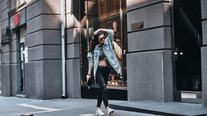 Młoda dziewczyna idzie po ulicy w denimowej kurtce koszulowej