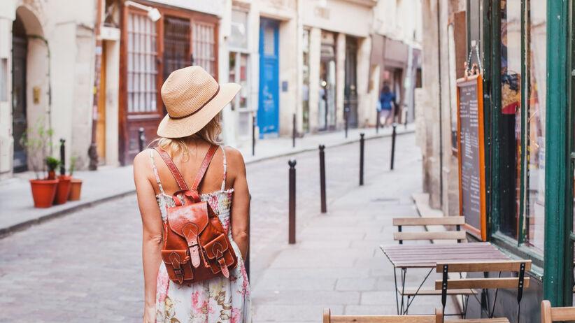 Młoda kobieta w sukience w stylu hiszpańskim i kapeluszu zwiedza miasteczko
