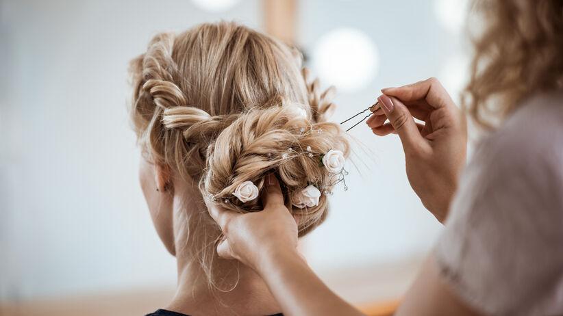 Fryzjer upina włosy młodej dziewczynie na jej własny ślub