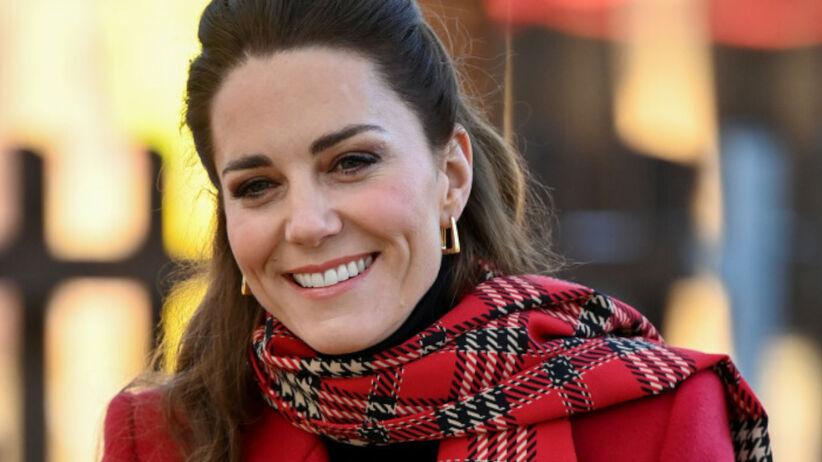 Księżna Kate uśmiechnięta w zakręconych włosach i czerwonym płaszczu