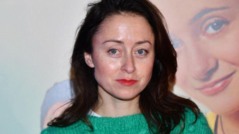 Natalia Przybysz w ciemnych włosach, zielonym swetrze i czerwonych ustach