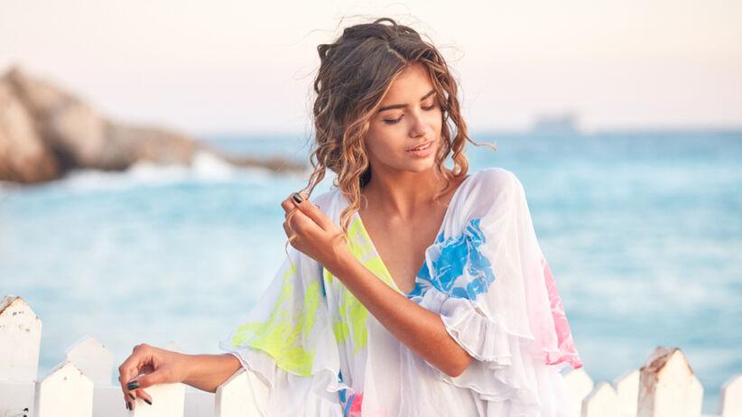 Młoda, opalona dziewczyna z delikatnymi falami na głowie stoi na plaży