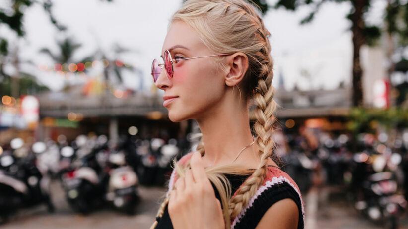 Młoda blondynka z warkoczami i w różowych okularach przeciwsłonecznych