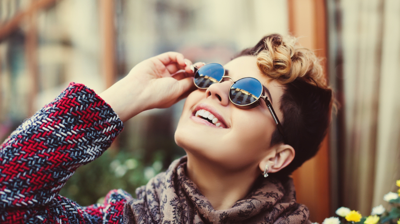 Młoda dziewczyna w okularach lenonkach z fryzurą pixie cut modną w 2021 roku