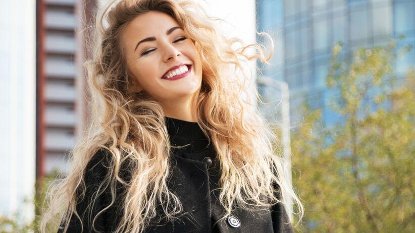 Uśmiechnięta dziewczyna z długimi blond włosami w odcieniu masła