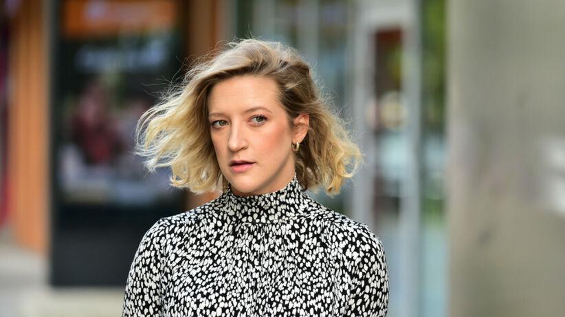 Lara Gessler z pofalowanymi włosami i w sukience w cętki idzie ulicą