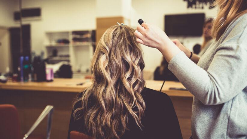 Kobieta robi u fryzjera modne słoneczne blond pasemka
