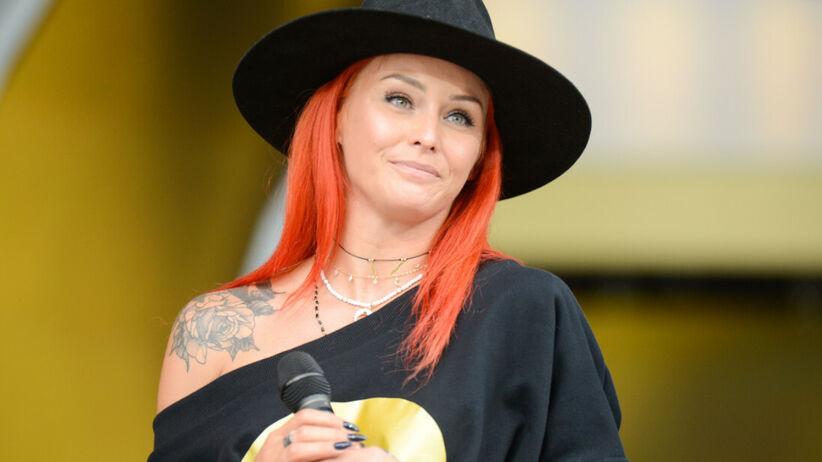 Ruda z Red Lips w kapeluszu cała na czarno na scenie i z mikrofonem