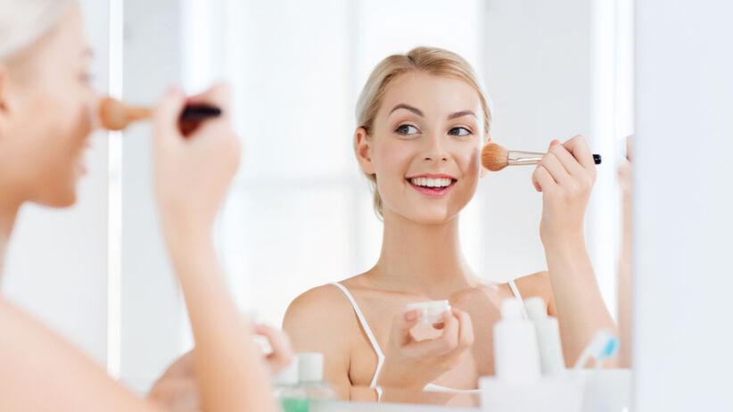 Blondynka stoi w łazience przed lustrem w białej koszulce i maluje się białym podkładem