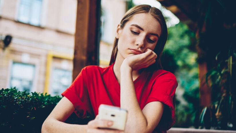 Młoda dziewczyna z cieniami pod oczami przegląda TikToka w telefonie