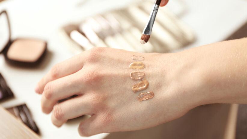 Kobieta dobiera odpowiedni podkład, testując różne odcienie na dłoni