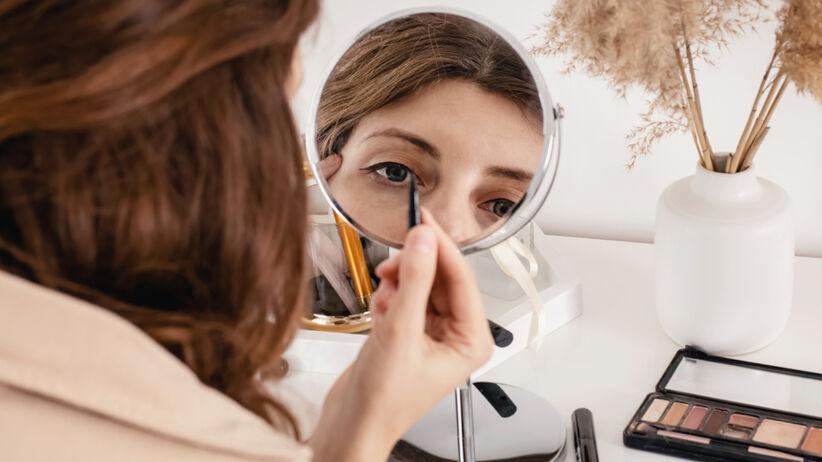 Kobieta maluje kreskę eyelinerem na powiece