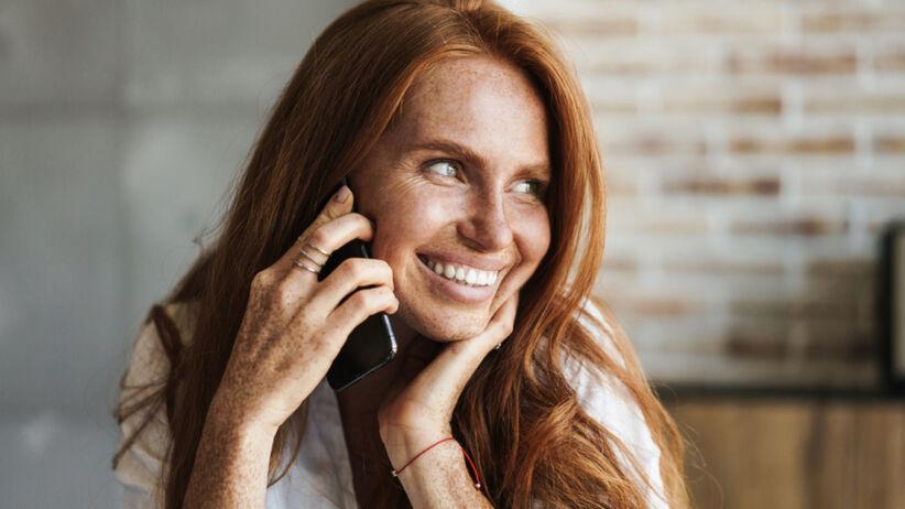 Rudowłosa uśmiechnięta kobieta z piegami rozmawia przez telefon
