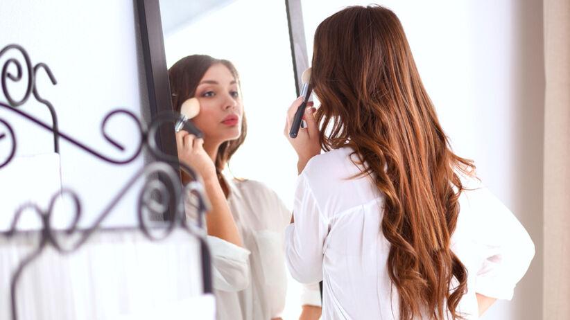 Piękna dziewczyna z młodą skórą maluje się przed lustrem