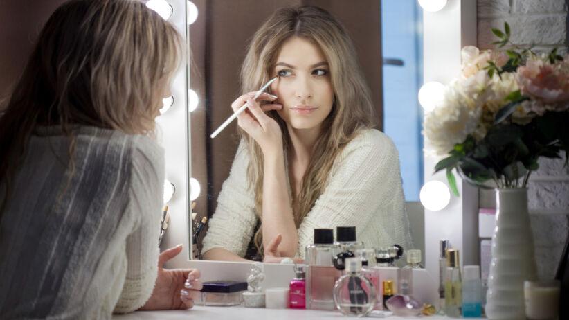 Młoda blondynka maluje się korektorem przed oświetlonym lustrem