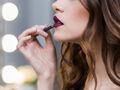 Kobieta maluje usta, żeby je powiększyć makijażem